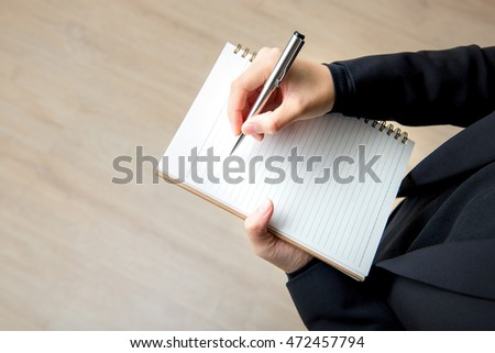Businesswoman hand writing on blank notebook with pen