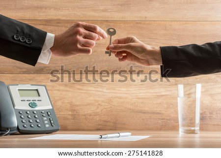 Businesswoman handing over a house key to a businessman in a conceptual image with their arms reaching across a desk with telephone and wooden background with copyspace. - stock photo