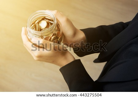 Businesswoman hands holding glass jar with coins - stock photo