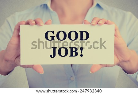Businesswoman hands holding white card sign with good job text message isolated on grey wall office background. Retro instagram style image - stock photo