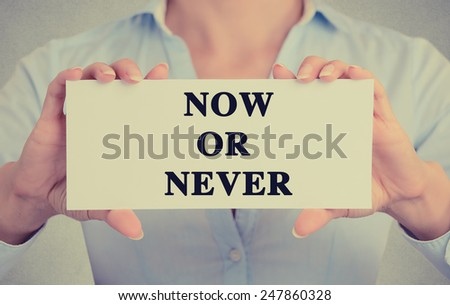 Businesswoman hands holding white card sign with now or never text message isolated on grey wall office background. Retro instagram style image - stock photo