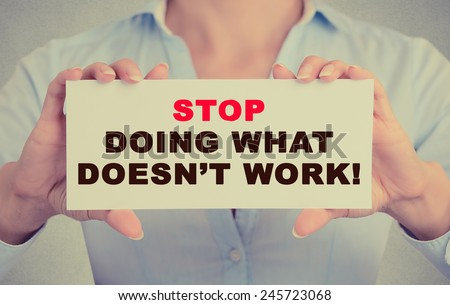 Businesswoman hands holding white card sign with Stop Doing What Doesn't Work text message isolated on grey wall office background. Retro instagram style image - stock photo