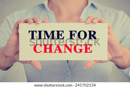 Businesswoman hands holding white card sign with time for change text message isolated on grey wall office background. Retro instagram style image. Smart strategy improvement concept  - stock photo