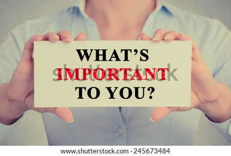 Businesswoman hands holding white card sign with What is important to you ? question text message isolated on grey wall office background. Retro instagram style image - stock photo