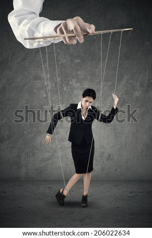 Businesswoman hanging on string and controlled by a hand - stock photo