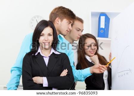 businesswoman happy smile, group of business people associates looking and pointing finger at a chart put up on the wall, white board, office