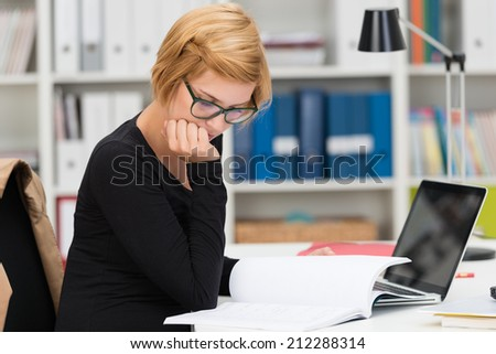 Businesswoman hard at work in the office sitting at her desk reading through paperwork with her chin resting on her hand - stock photo