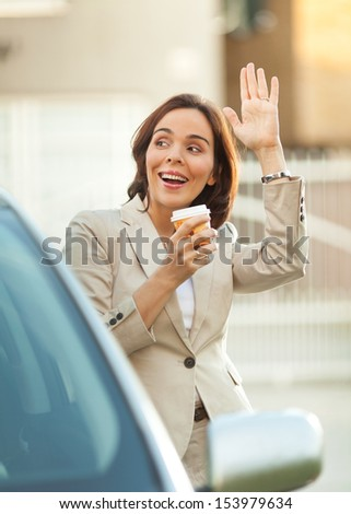 Businesswoman having a break and saying hello to someone. - stock photo
