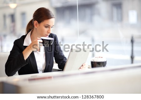Businesswoman having a cup of coffee while reading an article on her tablet computer. In a cafe. - stock photo