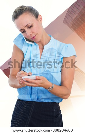 Businesswoman having a phone call and taking notes against skyscraper - stock photo