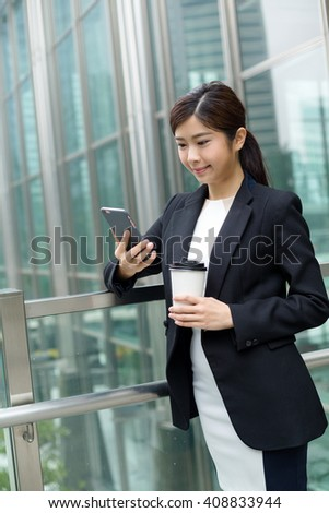 Businesswoman having coffee and look at cellphone