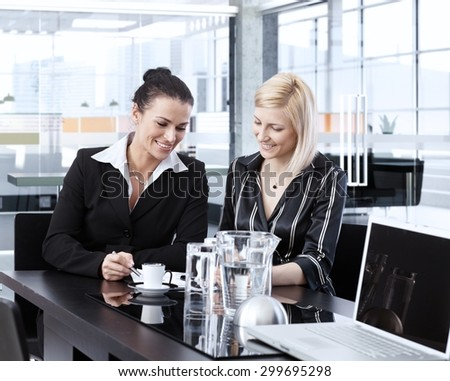 Businesswoman having coffee-break, talking, smiling at office.