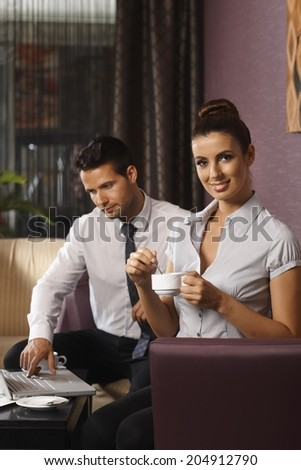 Businesswoman having coffee-break, while colleague working on laptop computer at hotel lobby. - stock photo