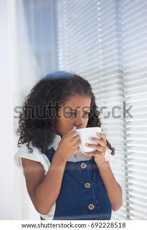 Businesswoman having coffee while standing by window in office