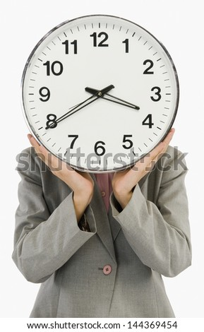 Businesswoman hiding her face with a clock - stock photo