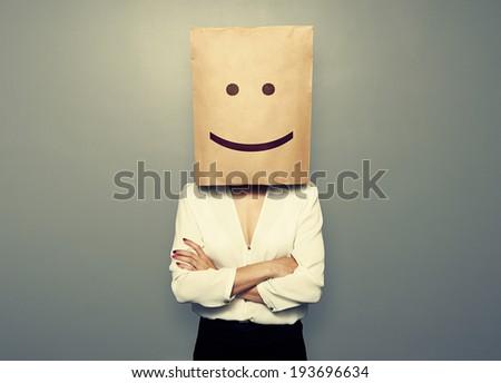 businesswoman hiding under smiley paper bag over dark background - stock photo