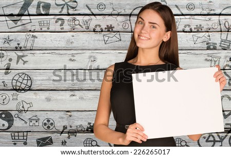 Businesswoman hold empty paper. Background of various social icons on old wooden surface