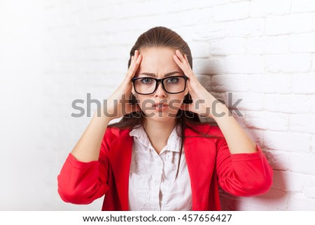Businesswoman hold hands on temples head, ache, pain depressed wear red jacket glasses stressed business woman over office wall