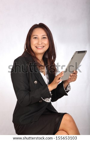 Businesswoman  hold tablet . Happy smiling mixed race Asian / Caucasian business woman busy.