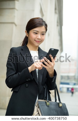 Businesswoman holding a bag and sending message on cellphone