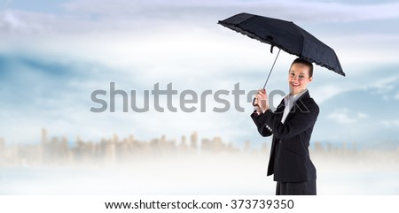 Businesswoman holding a black umbrella against large city on the horizon - stock photo