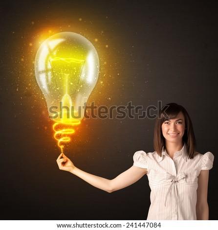 Businesswoman holding a shining, idea bulb - stock photo