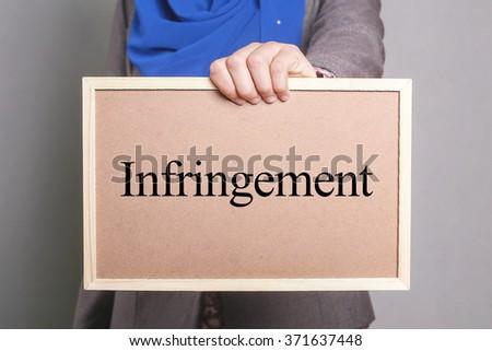 Businesswoman holding a softboard written Infringement - stock photo