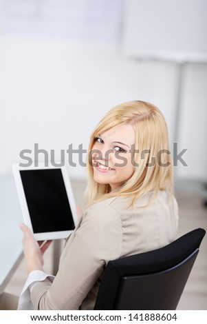 businesswoman holding a tablet in the office and looking back - stock photo