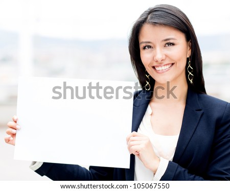 Businesswoman holding a white poster and smiling - stock photo