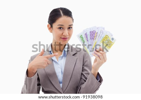 Businesswoman holding bank notes against a white background