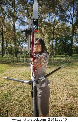 Businesswoman Holding Bow And Arrow Focused On Target - stock photo