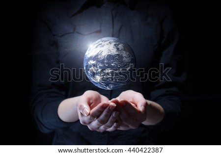 Businesswoman holding Earth planet in palm. Elements of this image are furnished by NASA