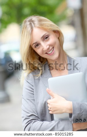 Businesswoman holding electronic tablet in town
