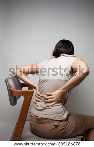 Businesswoman holding his hand to her aching back. - stock photo