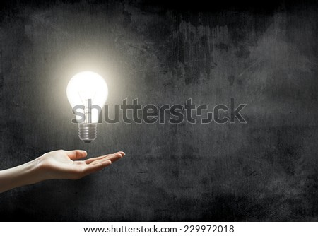businesswoman holding Light bulb lamp on blackboard background with copy space - stock photo