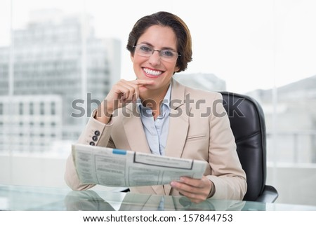 Businesswoman holding newspaper at her desk in bright office