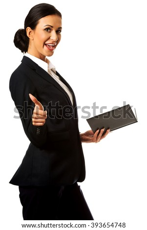 Businesswoman holding notes and showing thumb up