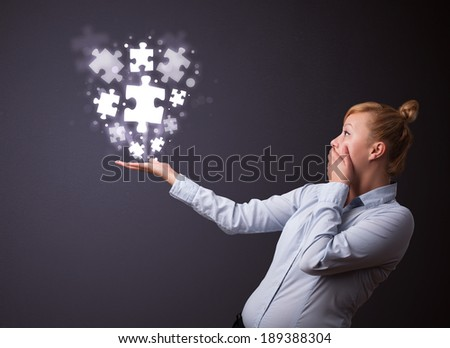 Businesswoman holding shining puzzle pieces in her hand - stock photo