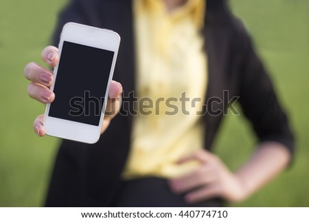 Businesswoman holding smartphone in hand, photo with depth of field - stock photo