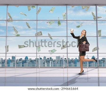 Businesswoman holding suitcase and coffee cup, looking at camera under money rain