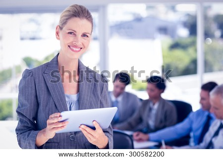 Businesswoman holding tablet and looking at camera in the office - stock photo