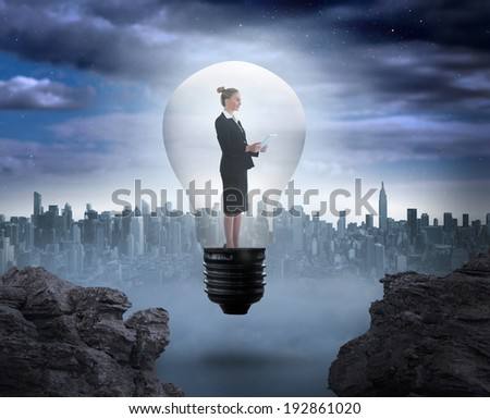 Businesswoman holding tablet in light bulb against large city on the horizon - stock photo