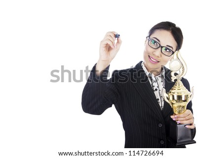 Businesswoman holding trophy while writing something on copy space - stock photo