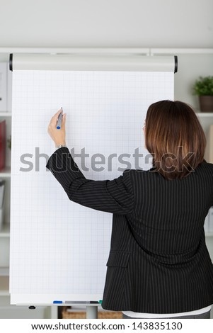Businesswoman in a black jacket standing with her back to the camera writing on a blank flipchart with a marker pen during a presentation - stock photo