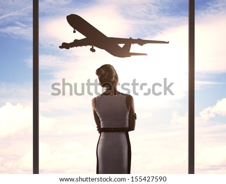 businesswoman in airport and airplane in sky - stock photo