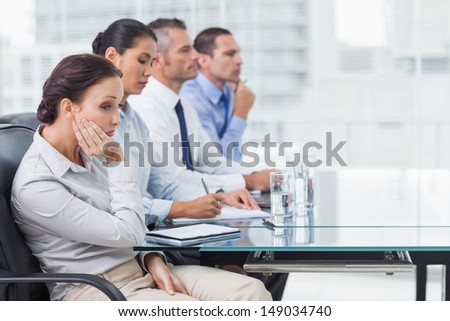Businesswoman in bright office getting bored while attending presentation - stock photo