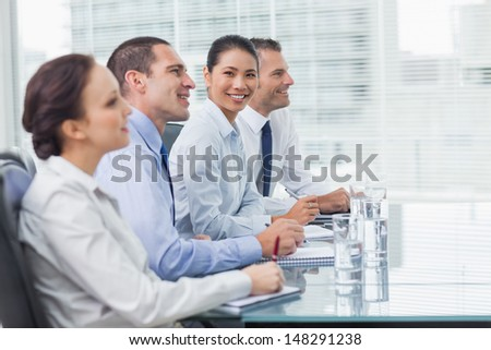 Businesswoman in bright office smiling at camera while her colleagues listening - stock photo
