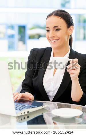 Businesswoman in cafe. Attractive young businesswoman in formalwear working on laptop and smiling while sitting in sidewalk cafe - stock photo
