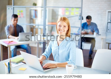 Businesswoman in casualwear looking at camera at workplace - stock photo