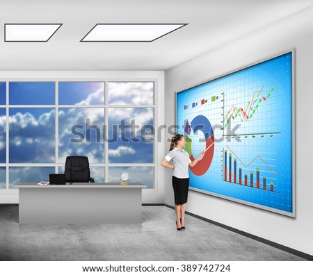 businesswoman in classroom pointing on  plasma panel with stock chart - stock photo